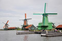 Dutch windmills on the Zaans river in Zaanse Schans, Netherlands. The well-preserved historical windmills with some relaxing tourists on the bank of Zaans river Stock Image