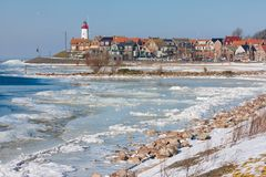Dutch winter landscape with frozen sea and drifting ice. At background view at lighthouse of fishing village Urk Royalty Free Stock Photography