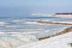 Dutch winter landscape with frozen sea and drifting ice. Dutch winter landscape with frozen sea and drifting ice near Urk. At background row of windturbines Stock Images