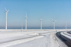 Dutch winter landscape with highway along wind turbines royalty free stock photos