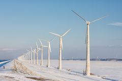 Dutch winter landscape with snowy field and wind turbines Stock Photo