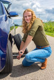 Dutch woman changing car tire on country road. Young european woman changing car tire on rural road Stock Images