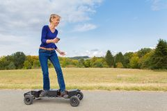 Dutch woman drives electric mountainboard in nature royalty free stock photography