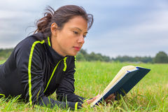 Dutch woman lying in grass reading book Royalty Free Stock Photos