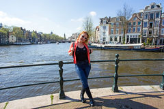 Dutch woman on a medieval bridge in Amsterdam Netherlands. Dutch woman on a medieval bridge in Amsterdam the Netherlands Stock Photography