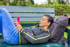 Dutch woman operating mobile phone lying on bench royalty free stock photography