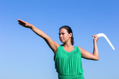 Dutch woman throwing boomerang in blue sky Stock Photo