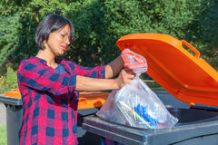 Dutch woman throwing plastic garbage in thrash bin Royalty Free Stock Images