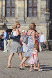Dutch women and child walk on Dam Square, Amsterdam, Netherlands. Stock Photography