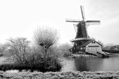 Dutch wood windmill standing near water Stock Images