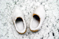 Dutch wooden shoes in the snow. A pair of dutch wooden shoes are left in the snow Royalty Free Stock Photo