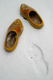 Dutch wooden shoes in the snow. A pair of dutch wooden shoes left an impression in the snow Stock Images