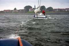 Dutch yacht in misery. With help of a tugboat Stock Photo