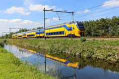 Dutch yellow and blue train in a green landscape Royalty Free Stock Image