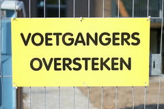 A Dutch yellow sign that says 'Pedestrians please traverse. A yellow Dutch sign near a building site that points pedestrians to traverse the road Royalty Free Stock Images