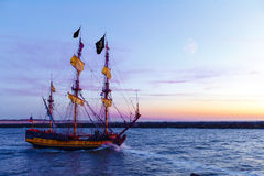 Dutchmen Pirate Ship and the moon. Pirate Ship leaving the harbor at the sunset for a long campaign against the loyal marines Stock Images