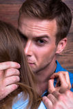 Dute and brutal man embraces, presses his girlfriend. Dute and brutal men embraces and presses his girlfriend to her by the head Royalty Free Stock Photo