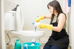 Young maid in yellow glove cleaning toilet bowl using brush and. Dutiful housewife cleaning toilet bowl with soap detergent and brush wearing black apron and Royalty Free Stock Image