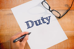 Duty against left hand writing on white page on working desk Stock Images