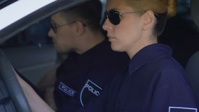 Duty cops in sunglasses getting in patrol car, ready to drive to crime scene. Stock footage stock footage