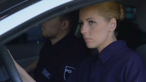 Duty police officers getting in patrol car, ready to drive to crime scene. Stock footage stock footage
