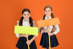We are on duty today. Pupil cleaning classroom. Nice and tidy. Schoolgirls mop ready for cleaning. School duties. Little. Helper. Girls cute kids school uniform stock images