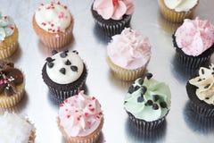 Dutzend sortierte kleine Kuchen auf silberner Oberfläche Stockfotografie