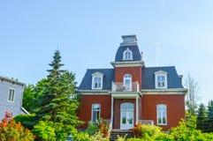Duur oud huis met reusachtige vensters Stock Afbeeldingen