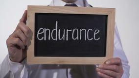 Duurzaamheid op bord in artsenhanden, hoop voor terugwinning, sterkte wordt geschreven die stock footage