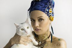 African style girl with a cat on your hands. Duvet in African-style clothes, blue headscarf. In the ears are big earrings. Holds a white cat royalty free stock photography