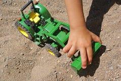Duwende het stuk speelgoed van de peuterhand vrachtwagen in het zand stock afbeeldingen