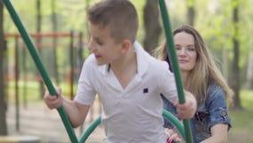 Duwende lachende zoon van de portret de leuke moeder op schommeling in een park Het mamma en het jonge geitje rusten actief in op stock videobeelden