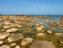 Duzi głazy w brzeg w gładkim falistym morzu linia brzegowa kamienista Zdjęcie Royalty Free