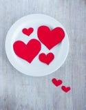 Duzi i mali serca na białym round talerzu Fotografia Stock