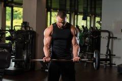 Duzi mężczyzna ćwiczenia bicepsy Z Barbell Zdjęcia Royalty Free
