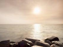 Duzi mokrzy głazy w brzeg w gładkim falistym morzu Kamieniści wybrzeży igrania fala Zdjęcia Royalty Free