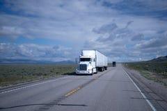 Duzi takielunki semi przewożą samochodem czarny i biały na Nevada drodze Zdjęcie Royalty Free
