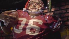 Dvärg av den amerikanska fotbollsspelaren i hjälm och den röda likformign med bollen inom stången arkivfilmer
