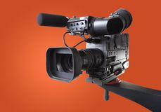 Dv camcorder on crane. Black dv-cam camera recorder on tv crane with orange background Stock Images