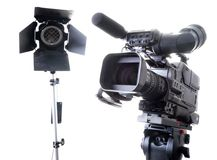 Dv camcorder and light. Isolated digital video camera recorder on tripod and spot light with white background Stock Images