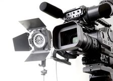 Dv camcorder and light. Isolated digital video camera recorder on tripod  and spot light with white background Stock Photography