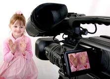 DV-camcorder shoot a girl. Stand dv-camcorder shoot a hands of little girl in pink dress Stock Photo