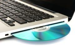 DVD ótico, movimentação de CD no laptop no fundo branco, close-up, isolado Imagem de Stock