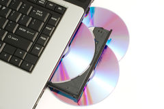 DVD or CD being loaded into laptop. CD or DVD being loaded into Laptop computer indicating piracy or home movie and music creation Stock Photo