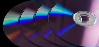 DVD Closeup. Closeup of four DVDs in a row with the light reflecting in a rainbow of color Royalty Free Stock Photo