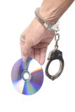 DVD in hand  with handcuffs Stock Photos