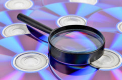 DVD and magnifier glass Stock Images