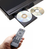 DVD player. Dvd–player with discs and the remote control in hand on a white background Stock Images