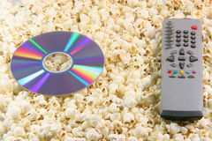 Dvd remote and popcorn. Television remote control and dvd disc movie on pop corn background food and entertainment conceps royalty free stock image