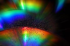 DVD- und CD-Diskette mit Wassertropfen färben Hintergrund Stockfotografie
